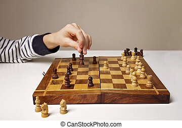 Child's hand holding chess figure while playing. Education, game, lifestyle concept.