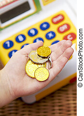Child's Hand Holding Pretend Coins Next To Toy Cash Register