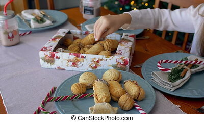 Child's hand reaching out to take christmas cookies -...