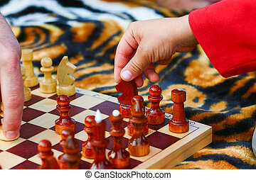 Child's hand takes a chess piece