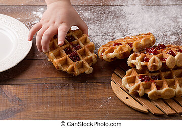 child's hand takes Tasty homemade waffle and strawberry jam