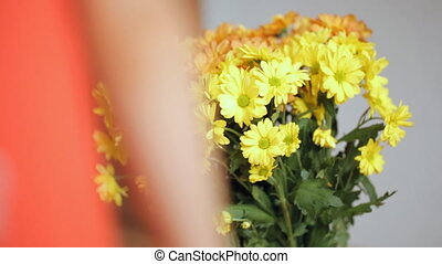 Child's hand touches yellow flowers passing by