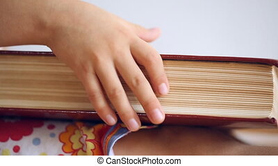 Child's hand turn over the pages