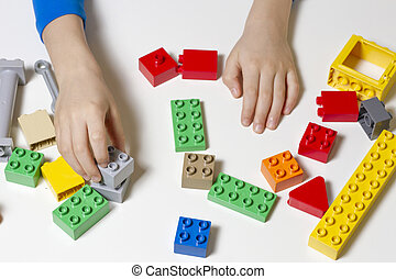 Child's hands and colorful toy building cubes. Top view