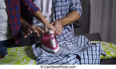 Child's hands ironing clothes with help of father