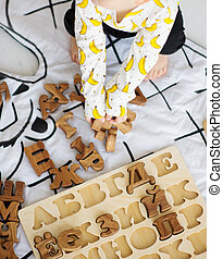 Child's hands playing with alphabet block