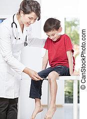 Child's neurologist testing knee reflex