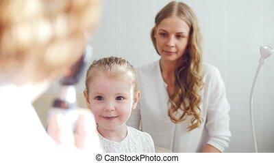 Child's ophthalmology - check up of eyesight - optometrist diagnosis little girl, close up