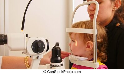 Child's ophthalmology - doctor optometrist checks eyesight...
