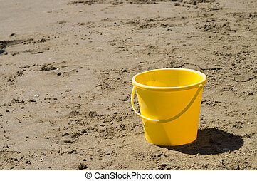 Child\'s pail - Yellow pail in beach