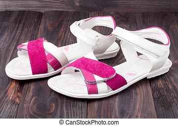 child's sandals on a dark wooden background