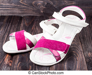 child's sandals on a dark wooden background