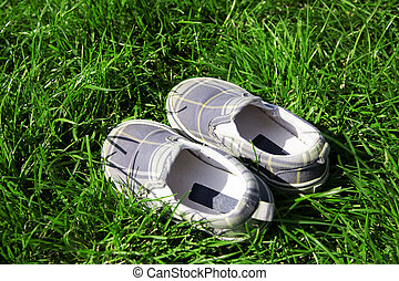 child's shoe for leisure in a green summer grass