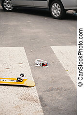 Child's skateboard and shoe on pedestrian crossing after collision with a car