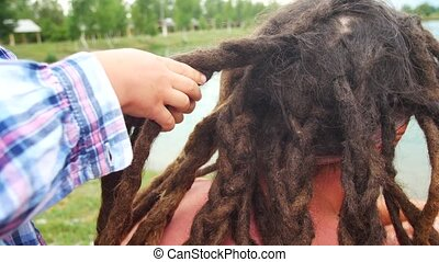 Childs weave braids to his dad from his dreadlocks. - Childs...