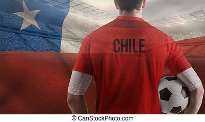 Chile Flag blowing in the wind at stadium with football player holding football