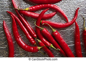 Chili hot peppers in red pattern over silver