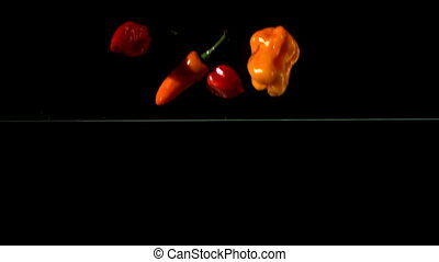 Chili peppers falling in water on black background in slow...