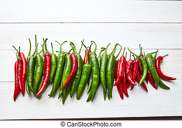 chili peppers in a row on a white wooden background