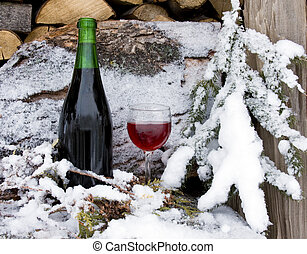 chilled red wine - bottle and glass of wine chilled by snow...
