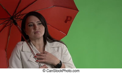 Chilled woman under red umbrella adjusting her coat against green screen