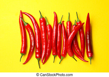 Chilli peppers on yellow background, top view