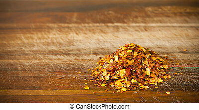 Chilli Seeds - Pile of red chilli seeds on a timber board