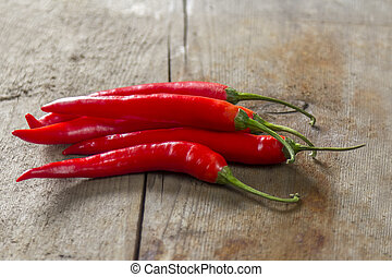 Chillies on wooden table - bunch of red chillies on rustic...