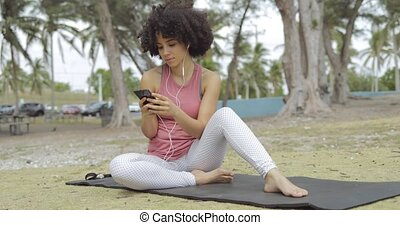 Chilling black girl using phone on mat - Content fit black...