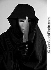 A person in a mask and a hooded cloak holding a butcher knife in a chilling, threatening manor.