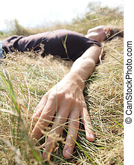 Young woman relaxing on the grass with a closeup of her hand
