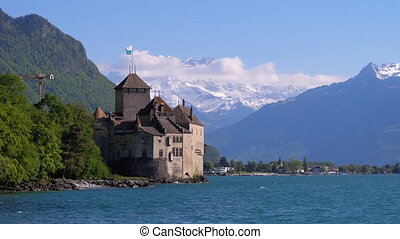 Chillon Castle at Geneva lake. Switzerland. Beautiful view of Chillon castle on the lake side of Geneva lake, with the peaks Dents du Midi of Swiss Alps in background, Montreux, Canton of Vaud, Switzerland