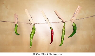 Chilly peppers hanging on a rope on a wooden background