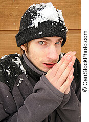 Young man shivers rubbing his hands together in the snow. He is wearing a beanie and a sweater.