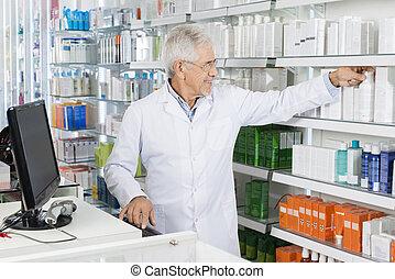 chimico, togliendo, bottiglia, da, mensola, mentre, lavorare computer