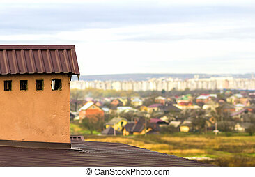 Chimney on a roof of a new built house with view of a city below