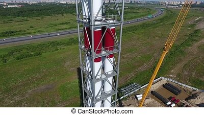 Chimney pipe construction aerial, fly back - A crane...