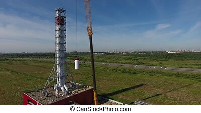 Chimney pipe construction aerial, the crane lifts the pipe...