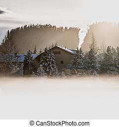Chimney smoke of a house in the cold mist in the high mountains