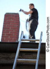 Chimney sweep at work on a roof with a ladder balanced against the guttering and focus to the ladder
