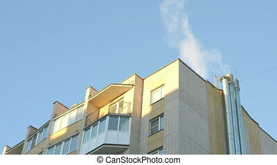 Chimney with white fume in the background blue sky