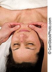 chin massage - a natural mature woman having a massage at...