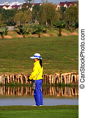 Golf caddie of China waiting for th shot