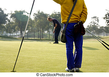 Golf caddie of China holding the pin for a golfer