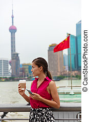 China phone Asian professional woman using cellphone during commute to work by the Bund river in Shanghai, chinese lifestyle.