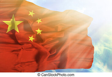 China waving flag against blue sky with sunrays