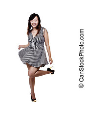 Chinese American Woman Twirling In Checkered Dress Smiling With Leg Up