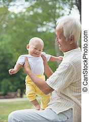 chinese asian grandfather having fun with his grandson outdoor