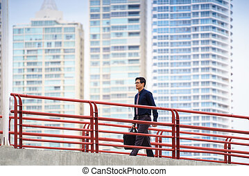 Portrait of chinese businessman walking on bridge in Panama, commuting to work. Skyscrapers in background