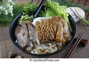 Chinese bowl of vermicelli noodle with fried beef, cow's stomach and salad on the table